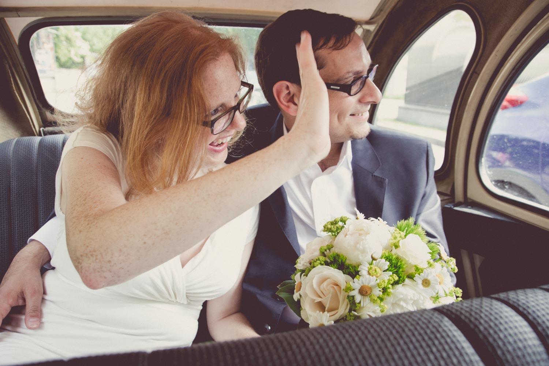 Fröhliches Winken der Braut aus dem historischen Brautauto nach der Hochzeit - die Gäste und das Brautpaar auf dem Weg zur Hochzeitsfeier am Deiniger Weiher