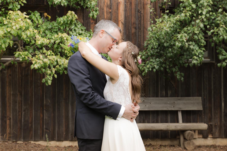 Kuss auf der Wiese, bevor es zur Trauung geht - Hochzeitsfotos