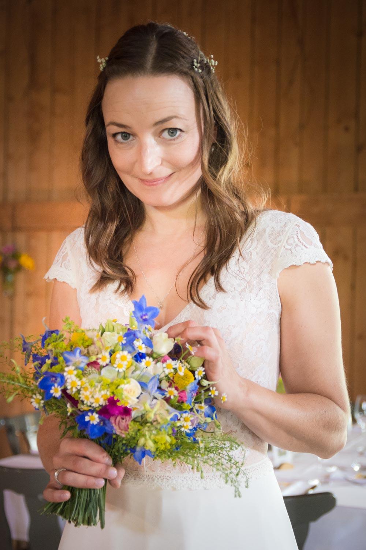Die hübsche Braut mit ihrem sommerlichen Brautstrauß