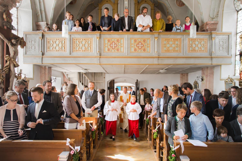 Einzug von Braut und Bräutigam in die Dorfkirche - die Gäste stehen, der Pfarrer geht voran - Hochzeitsfotos