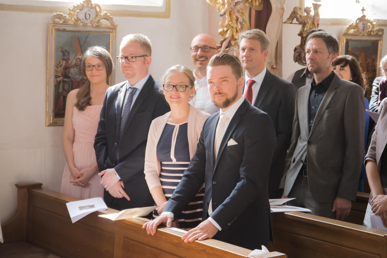 Emotionaler Moment bei der katholischen Trauung - die Gäste stehen, das Brautpaar gibt sich das Ja-Wort - Hochzeitsfotos