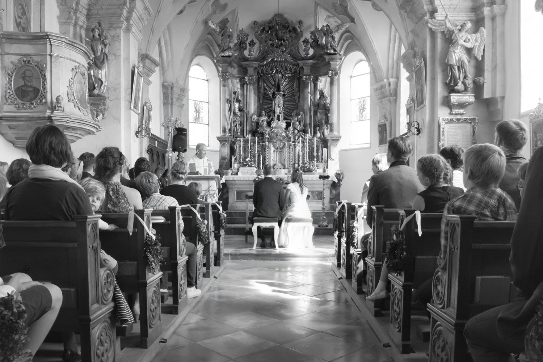 Der Pfarrer bei der Traupredigt - Braut, Bräutigam und die gesamte Hochzeitsgesellschaft hören ihm in der kleinen Dorfkirche zu