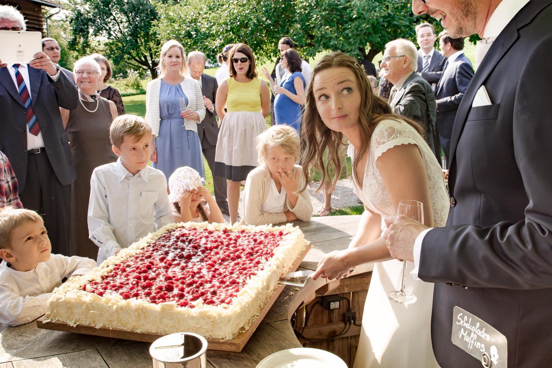 Die Braut schneidet die Torte an, die Gäste schauen zu. Ein wichtiger Moment bei der Sommerhochzeit am AmVieh-Theater