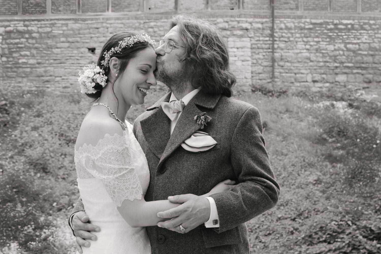 Umarmung im Burggraben von Burg Lohra - der glückliche Bräutigam küsst eine strahlende Braut auf die Stirn, die Hochzeitsfotografin ist ganz nah dran - Hochzeitsfotos