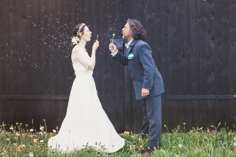 Spaß beim Brautshooting - die Eheleute freuen sich über die Wiese mit Pusteblumen, auch der Hochzeitsfotografin gefällt das Motiv - Hochzeitsfotos