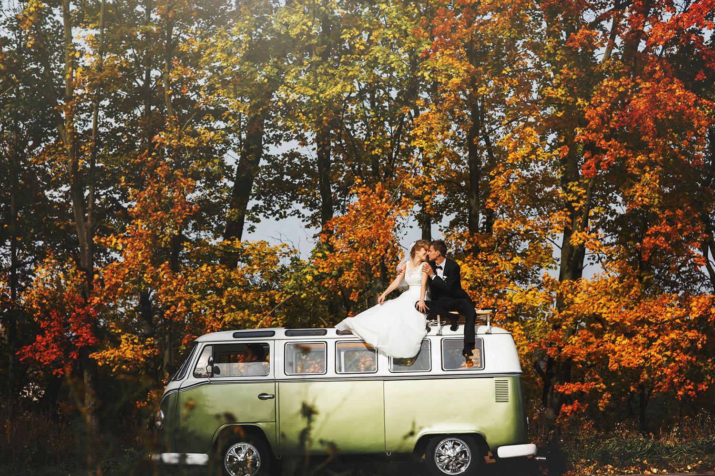 Innovatives Hochzeitsfoto mit dem Brautpaar auf dem Dach eines VW Bus - Hochzeitsfotos