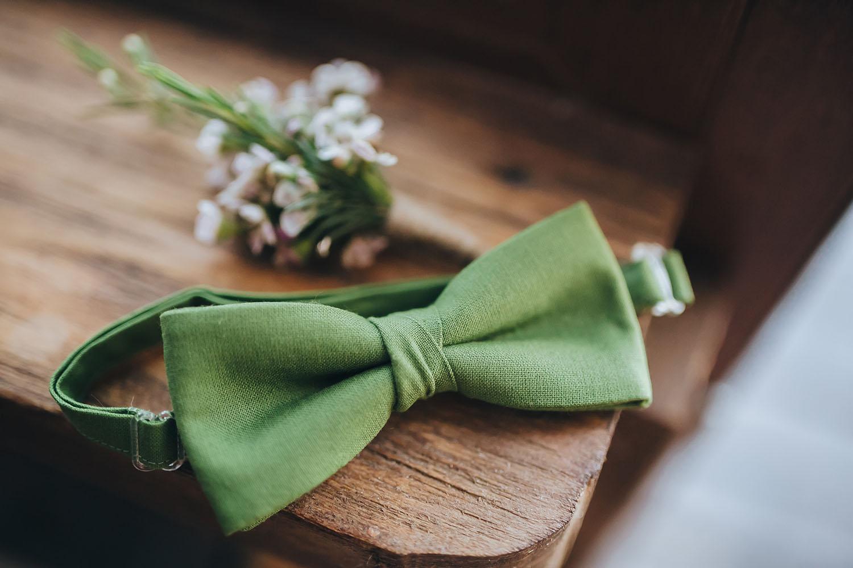 Die grüne Fliege des Bräutigams auf Holzbalken mit Blumen im Hintergrund