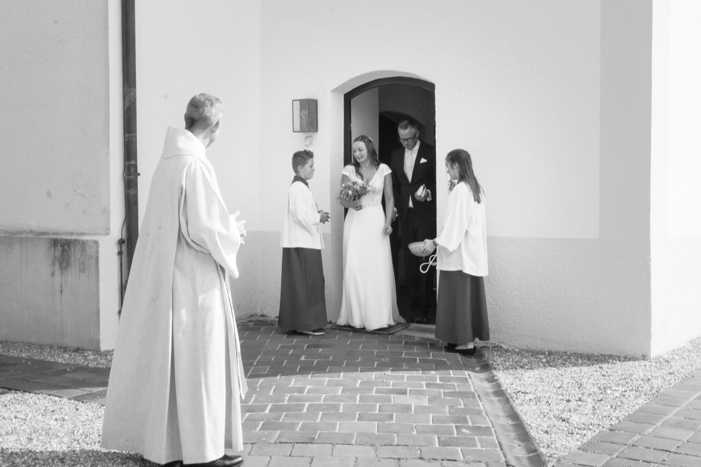Hochzeitspaar beim Auszug aus der kleinen Dorfkirche im Osten von München