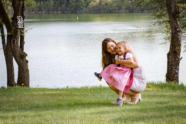 Die junge Mutter spielt mit ihrer Tochter auf diesem Hochzeitsfoto nach der freien Trauung am Restaurant Steinsee - Hochzeitsreportage München