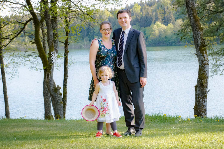 Die junge Familie posiert für die Hochzeitsfotografin nach der freien Trauung am Restaurant am Steinsee bei Zorneding