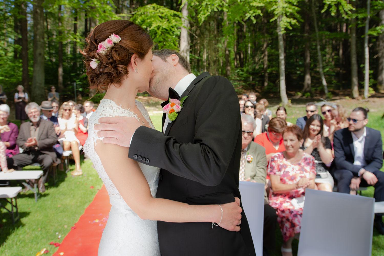 Braut und Bräutigam küssen sich nach der freien Trauung am Steinsee bei Zorneding