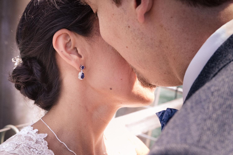 Ein Detail des Brautpaars - der Bräutigam flüstert seiner Braut etwas ins Ohr