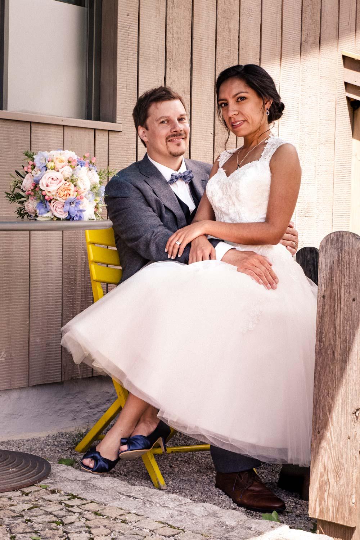 Die Braut sitzt auf dem Schoß ihres Bräutigams am Ufer des Tegernsee in Rottach-Egern