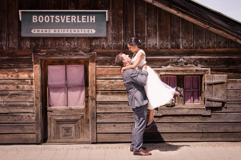 Der Bräutigam hebt seine Braut für dieses Hochzeitsfoto in Rottach-Egern am Tegernsee
