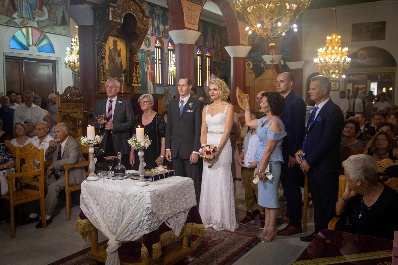 Die griechische Braut und ihr deutscher Bräutigam bei ihrer griechischen Hochzeit am Altar, neben ihnen stehen ihre Eltern.