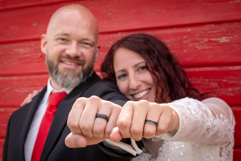 Das Brautpaar zeigt stolz die Eheringe auf diesem Hochzeitsfoto am Alpaka Beach