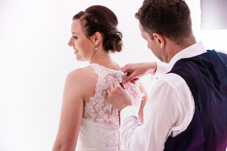 Der Bräutigam hilft der Braut vor der Trauung ins Kleid - auch diese Szene darf eine gute Hochzeitsfotografin nicht verpassen - Hochzeitsreportage München