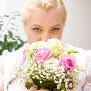 Die Braut in Tracht riecht am Brautstrauß und schaut in Richtung Hochzeitsfotograf