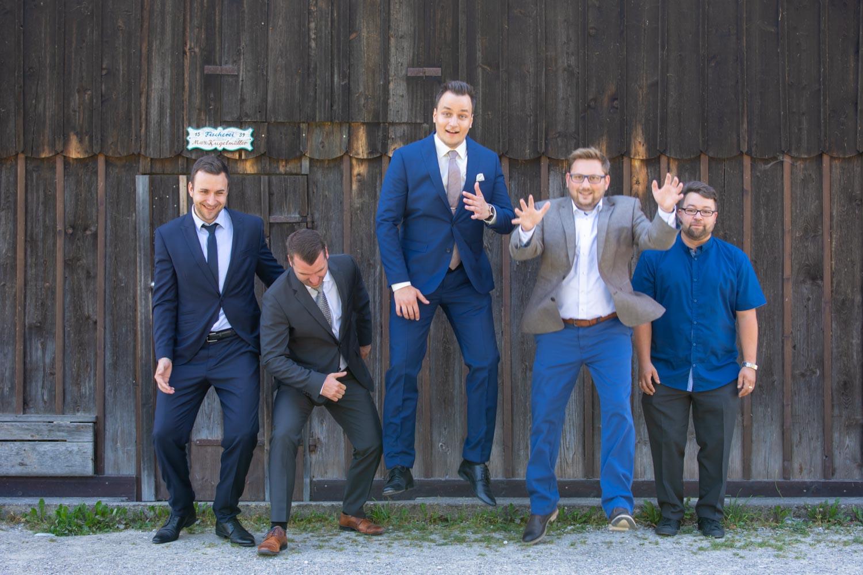 Der Bräutigam und die männlichen Gäste springen für das Gruppenfoto - Hochzeitsreportage München