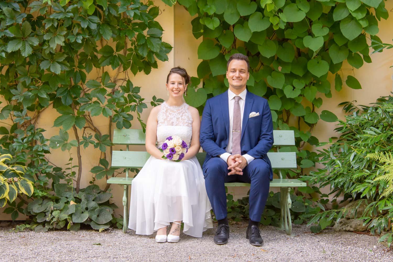 Braut und Bräutigam beim Hochzeitsfoto auf einer Bank auf der Roseninsel im Starnberger See