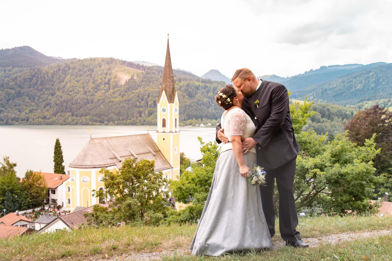 Das Brautpaar in Tracht küsst sich auf diesem Hochzeitsfoto mit Blick auf Sankt Sixtus am Schliersee