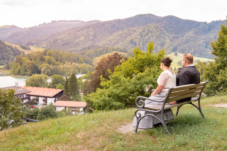 Das Brautpaar entspannt vor der Trauung in Sankt Sixtus auf einer Parkbank am Schliersee - Hochzeitsreportage München