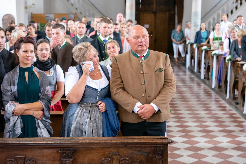 Die gerührten Eltern der Braut während der Trauung in St. Sixtus am Schliersee