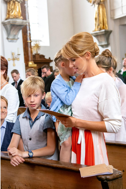 Eine junge Mutter mit ihren Kindern beim Gottesdienst in de Kirche - Hochzeitsfotos