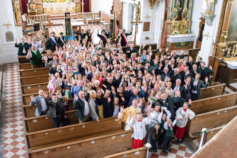 Gruppenbild der Hochzeitsgesellschaft mit dem Priester / Pfarrer in der Kirche St. Sixtus in Schliersee - Hochzeitsfotos