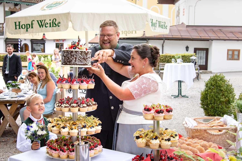Das Brautpaar in Tracht schneidet am Hotel Terofal in Schliersee die außergewöhnliche Hochzeitstorte an
