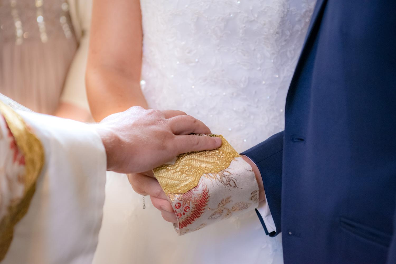 Die Hände von Braut und Bräutigam bei der Segnung durch den Priester während der Trauung