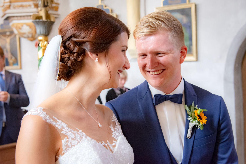 Das glückliche Brautpaar in der Kirche, der Ehemann strahlt seine frische Ehefrau an
