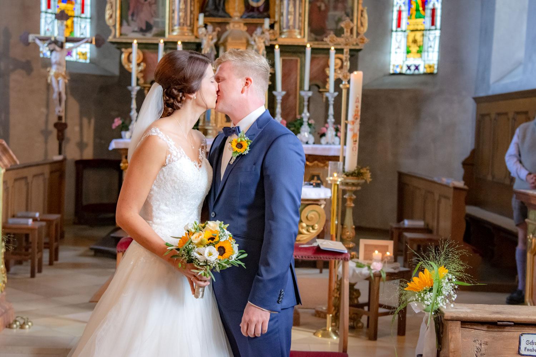 Braut und Bräutigam küssen sich nach dem Ja-Wort in der Kirche in Hausham am Schliersee