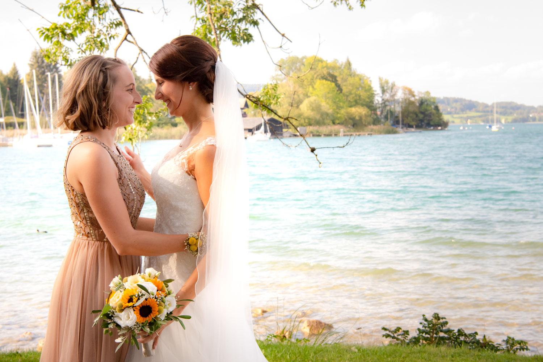 Die Hochzeitsfotografin fotografierte diese Szene der Braut mit ihrer besten Freundin in Bad Wiessee am Seeufer des Tegernsee kurz nach der Trauung in Hausham
