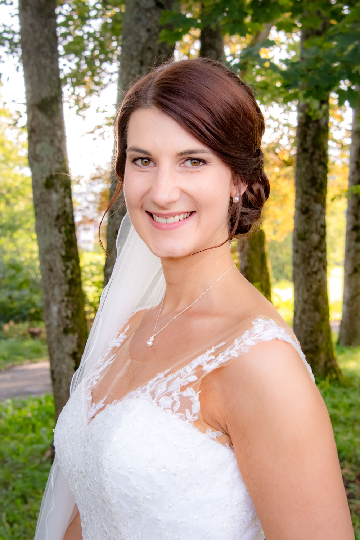 Die Braut strahlt für die Hochzeitsfotografin im Park in Bad Wiessee am Tegernsee - Hochzeitsreportage München