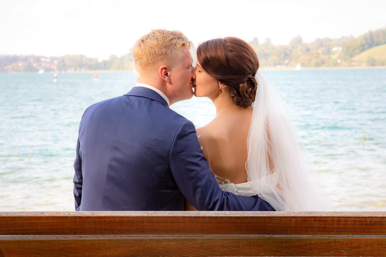 Das Brautpaar küsst sich auf einer Bank in Bad Wiessee am Ufer des Tegernsee süflich von München