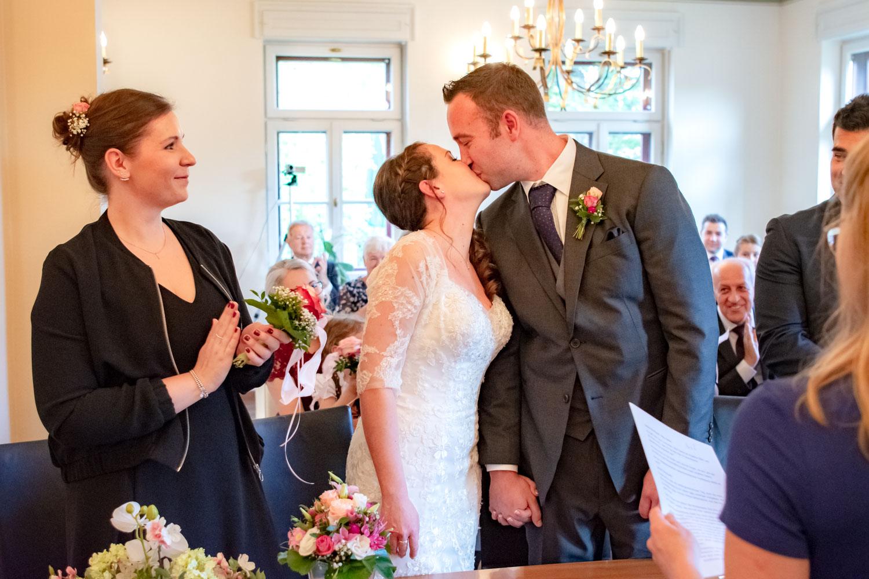Das Brautpaar küsst sich im Standesamt Unterföhring, die Gäste und die Trauzeugin applaudieren - Hochzeitsreportage München