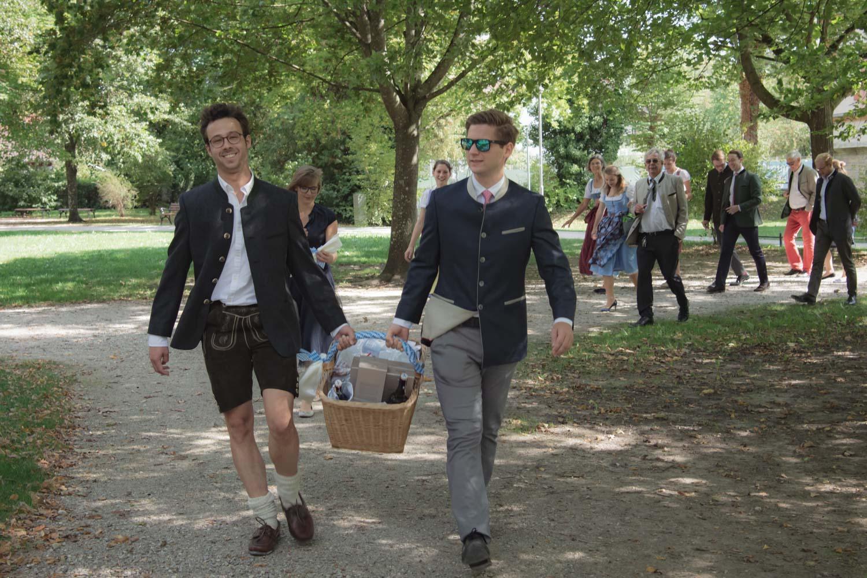 Die Gäste in Tracht gehen nach der Trauung im Kurparkschlösschen in Herrsching am Ammersee zur Hochzeitsfeier - Hochzeitsreportage München