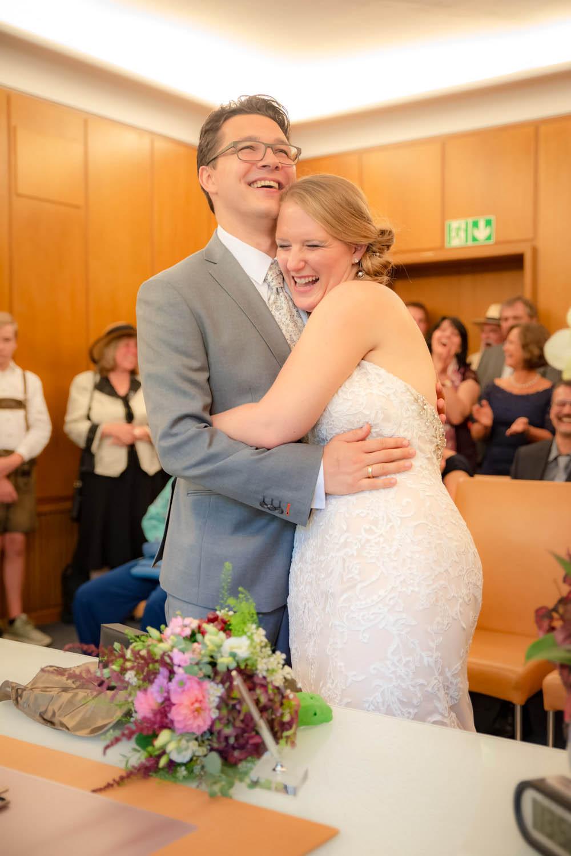 Die strahlende Braut umarmt ihren Ehemann im Standesamt an der Mandlstraße in Schwabing - Hochzeitsreportage München