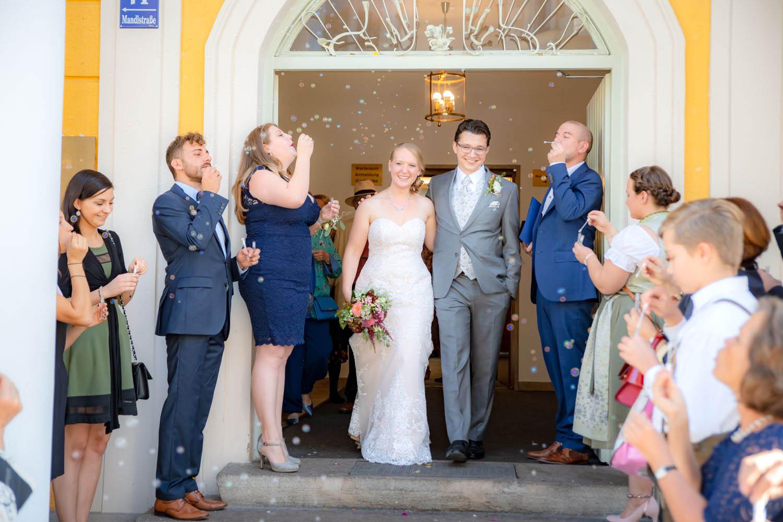 Das frische Ehepaar verlässt das Standesamt Mandlstraße, ihre Gäste begrüßen sie bei tollem Wetter mit Seifenblasen - Hochzeitsreportage München