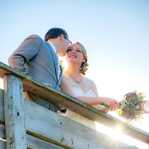 Bei strahlendem Sonnenschein flüstert der Bräutigam seiner Braut etwas ins Ohr