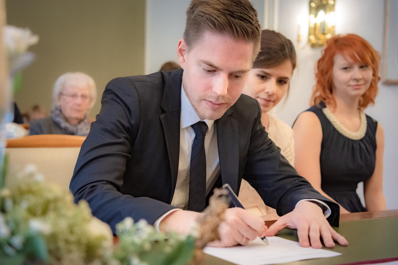 Die erste Unterschrift als Ehemann vor dem Standesbeamten in der Mandlstraße, die Braut schaut zu - Hochzeitsreportage München
