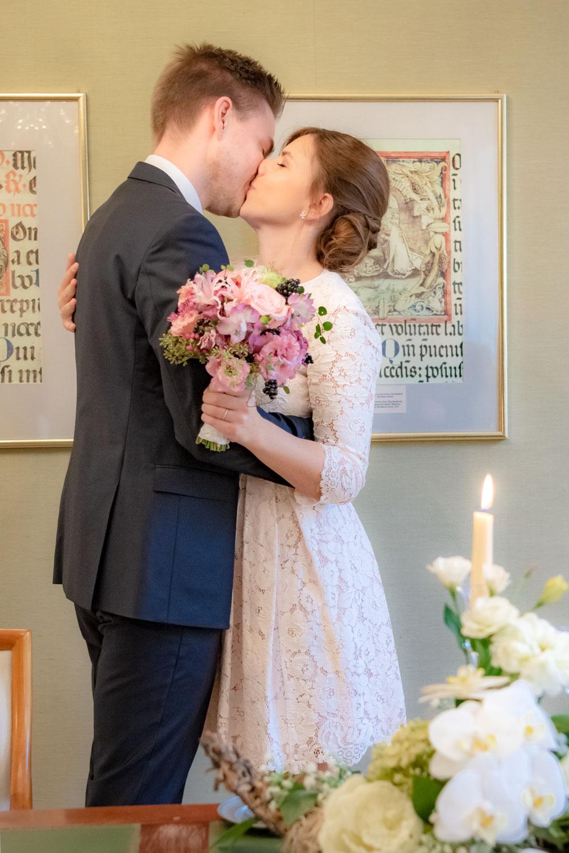 Die Braut hält ihren Brautstrauß und küsst ihren Ehemann an der Mandlstraße - Hochzeitsreportage München