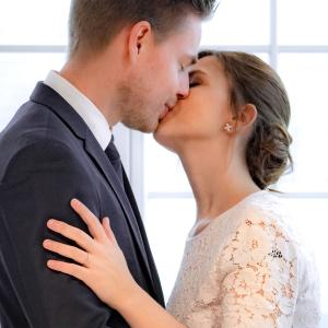 Das Brautpaar küsst sich am Fenster mit Blick auf den Tegernsee
