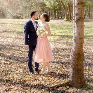 Der Bräutigam und seine Braut im rosa Brautkleid küssen sich im Park am Waldhaus zur alten Tram bei Grünwald