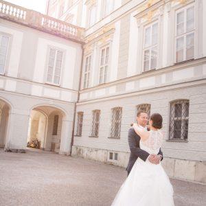 Eng umschlungen steht das Brautpaar im Hof von Schloss Nymphenburg in München
