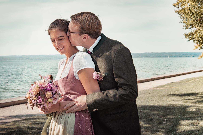 Der Bräutigam küsst seine Braut am Ufer des Ammersee in Herrsching
