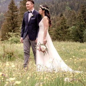Hand in Hand steht das Brautpaar auf der Frühlingswiese am Festgelände