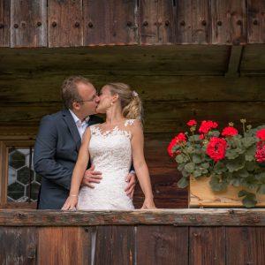 Innig küsst sich das Brautpaar auf dem Balkon eines alten Hofs im Wasmeier Freilichtmuseum