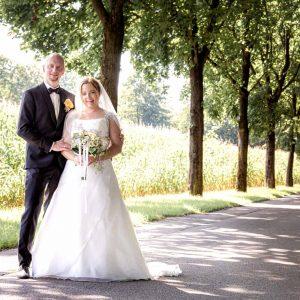 Ein klassisches Brautpaarportrait vor Maisfeld - nach der Hochzeit geht es dann weiter zum Hotel Bauer